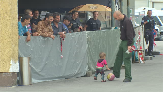 stockvideo's en b-roll-footage met exterior shot of a polizei police officer stopping to play football with a young migrant refugee child cute sweet heartwarming clip note... - polizei