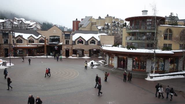 Exterior shot of a Whistler Village sign covered in snow in British Columbia Cananda Wide shot of visitors walking through a shopping plaza in...