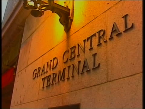 exterior shot of grand central station. shot begins with close up of grand central terminal sign and pans to show people walking along street and... - back lit video stock e b–roll