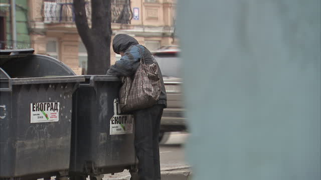 Exterior shot of homeless poor Ukrainian man going through dumpster bin in derelict part of Odessa town on January 21 2015 in Odessa Ukraine