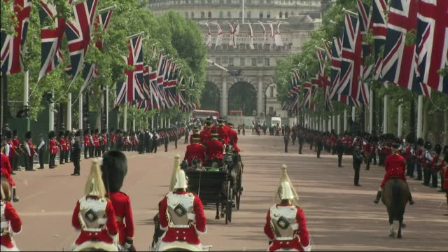 Exterior shot of hores drawn carriages carrying Meghan Duchess of Sussex and Prince Harry Duke of Sussex share a horse drawn carriaged with Camilla...