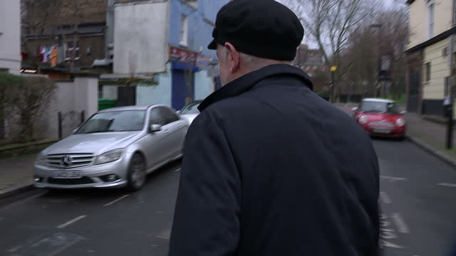 exterior shot of jeremy corbyn leader of the labour party leaving his home wearing a black flat cap hat says 'so nice to see you bye' and walks off... - イズリントン点の映像素材/bロール