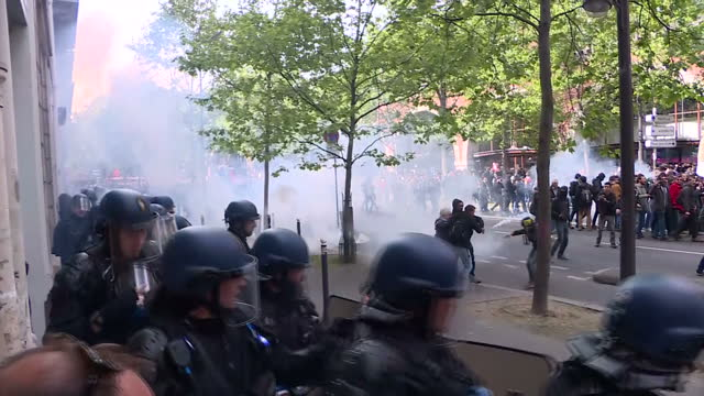 vídeos de stock, filmes e b-roll de exterior shot of line of french police officers in riot gear walking down street as tear gas is being fired in street smoke and chaos as different... - 1 de maio