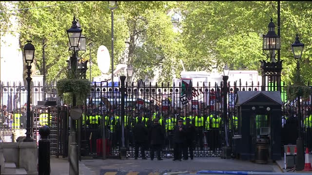exterior shot of london eye pan down to a long shot of anticonservative protesters behind police lined gates of downing street with banners and... - general election stock videos & royalty-free footage