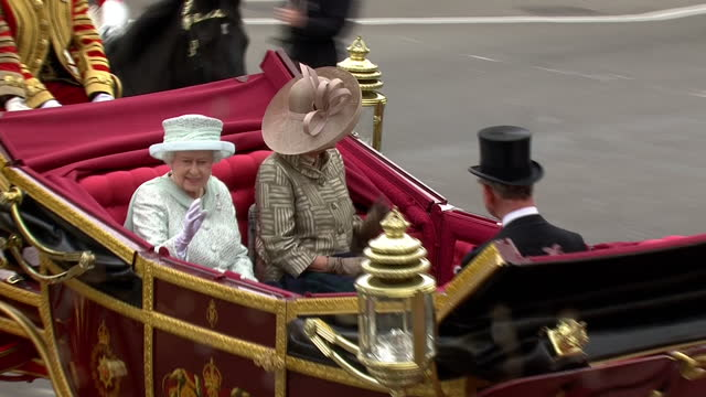 exterior shot of queen elizabeth ii arriving at buckingham palace to cannon salute in horse drawn carriage with prince charles and camilla duchess of... - cannone video stock e b–roll