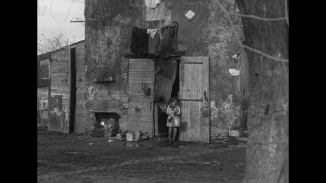 Exterior shot of ramshackle homes / parents and children leave room carrying different objects / family all six children now appearing leave house...
