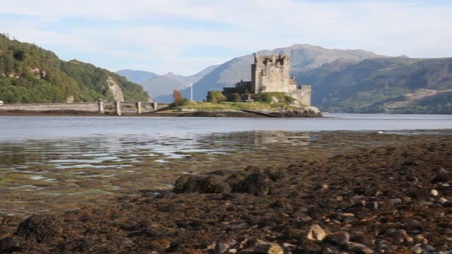 exterior shot of the eilean donan castle on an island in loch duich is only accessible via a stone bridge - dornie stock videos & royalty-free footage