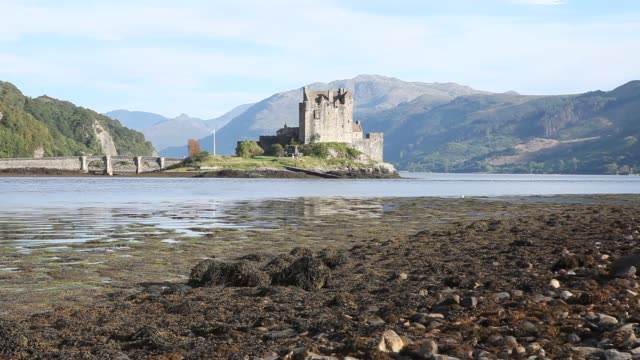 exterior shot of the eilean donan castle on an island in loch duich is only accessible via a stone bridge. - scottish flag stock videos & royalty-free footage