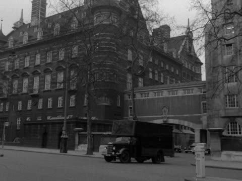 exterior shot of the embankment side of the new scotland yard building a van pulls out from the building and traffic moves past in the foreground 1958 - ロンドン ホワイトホール点の映像素材/bロール