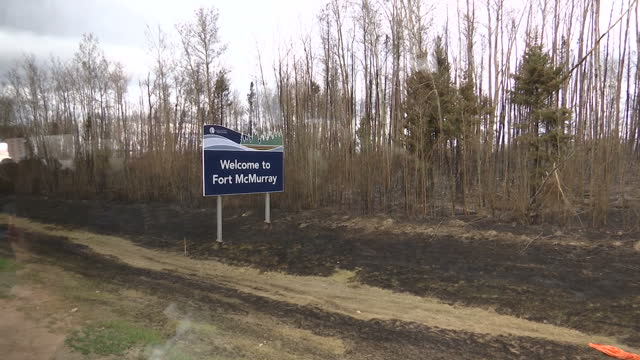 Exterior shot of 'Welcome to Fort McMurray' sign surrounded by burnt landscape on May 10 2016 in Alberta Canada
