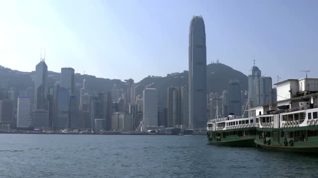 exterior shot passenger ferry moored in harbour / exterior shot hong kong skyline across harbour with ferries moored in foreground / exterior shots... - ponte di una nave video stock e b–roll