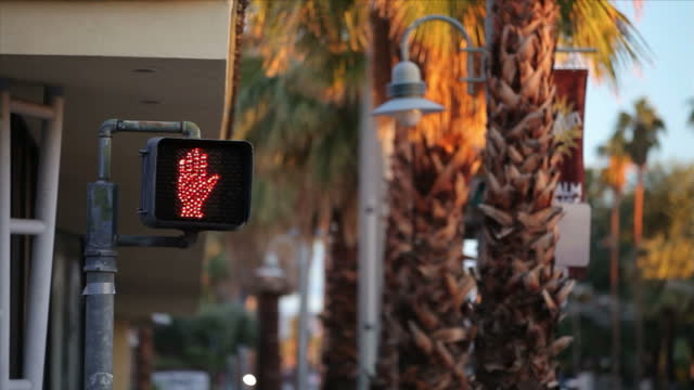 Exterior shot pedestrian crossing signal showing a walk then stop sign on a Palm Springs highstreet with sun setting against the trees on 7th...