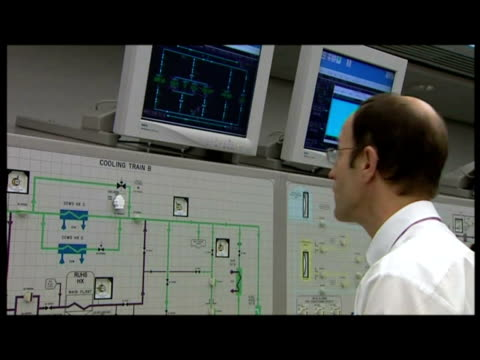 exterior shot pylons & power lines. interior shots workers operating switches in control room. - イーストアングリア点の映像素材/bロール