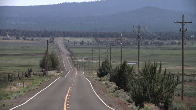 exterior shot road running into distance through the klamath falls countryside with the cascade range mountains in the distance on may 21 2014 in... - オレゴン州点の映像素材/bロール