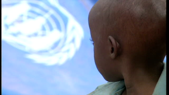 exterior shot rwandan refugee child sitting looking at unhcr logo in background on june 16 1994 in various cities rwanda - völkermord stock-videos und b-roll-filmmaterial