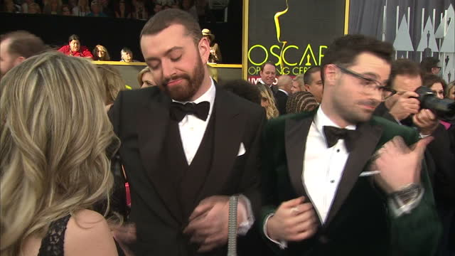Exterior shot Sam Smith and Jimmy Napes nominated for Best Original Song on Academy Awards red carpet talking about being drunk on Golden Globes red...