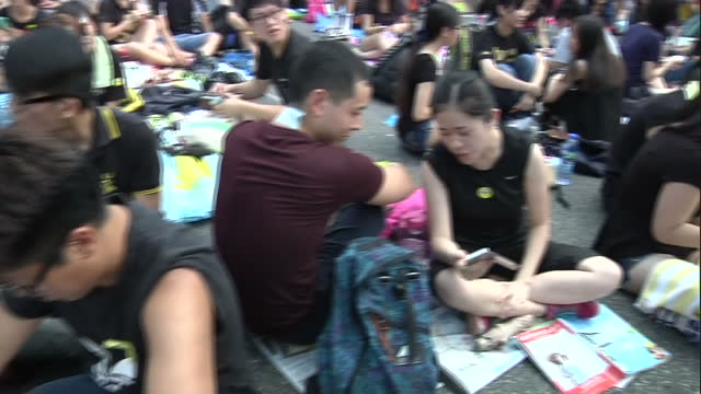 exterior shot showing prodemocracy protesters on mobile phones using fire chat social media platform gathered on streets of financial district in... - central district hong kong stock videos and b-roll footage