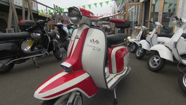 vídeos de stock, filmes e b-roll de exterior shot wheeling 1963 lambretta tv 175 scooter moped out at dealership red and white classic retro vintage style with close up of flag logo... - vanguardista