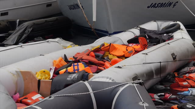 KOS Exterior shots abandoned migrant inflatable boat filled with discarded life jackets / exterior shot flotilla of abandoned boats
