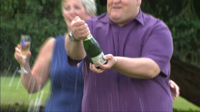 exterior shots adrian & gillian bayford pop cork on bottle of champagne & pose for the media with large cheque for million pounds euro million... - 宝くじ点の映像素材/bロール
