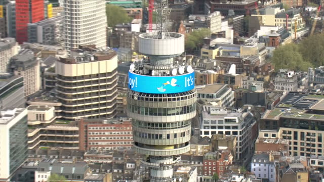 vídeos de stock e filmes b-roll de exterior shots aerials of bt tower in london showing the message ''it's a boy'' in honour of the birth of prince william's third child on 23 april... - bt tower londres