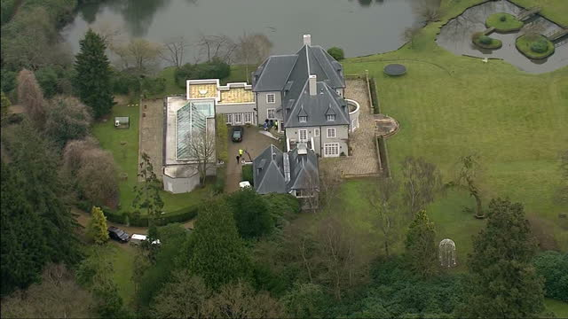 exterior shots aerials over the home of boris berezovsky showing police forensic chemical experts outside the entrance home of boris berezovsky... - 実業家 ボリス・ベレゾフスキー点の映像素材/bロール