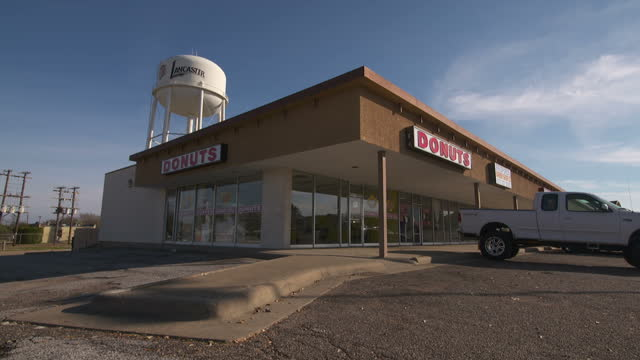 exterior shots african american woman talking on mobile phone outside rundown looking donut and barbers shops on december 11 2015 in lancaster texas - barber stock videos and b-roll footage