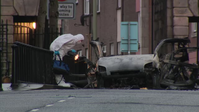 exterior shots aftermath of bombing in londonderry crime scene tape remains of car and forensics officers checking evidence and examining scene... - ロンドンデリー点の映像素材/bロール