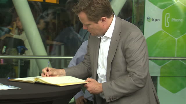 exterior shots ahmad jauhari yahya ceo of malaysia airlines and colleagues signing the book of condolences for mh17 victims - signierstunde stock-videos und b-roll-filmmaterial