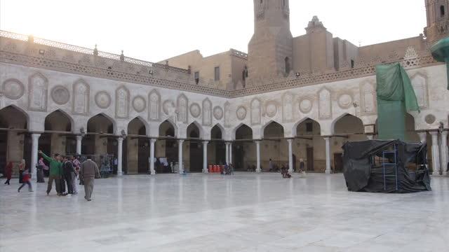 exterior shots al-azhar mosque buildings, muslim people walk around mosque on february 2, 2016 in cairo, egypt. - モスク点の映像素材/bロール