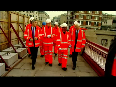 exterior shots Alistair Darling Chancellor Gordon Brown Prime Minister wearing flourescent orange jackets walk with National Rail site workers as...