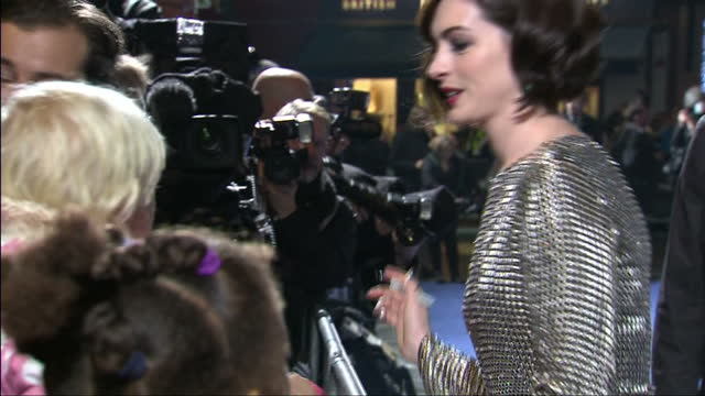 exterior shots Anne Hathaway signing autographs and posing for fan photos on red carpet