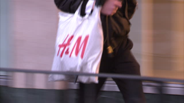 exterior shots anonymous shoppers walking along high street carrying plastic bags and paper bags. on in ealing, england. - shopping bag stock videos & royalty-free footage