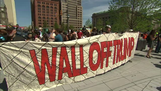 """exterior shots anti donald trump protesters holing banner and placards, """"wall off trump"""", """"let's kick some intolerant ass with compassion"""", """"the... - holing stock videos & royalty-free footage"""