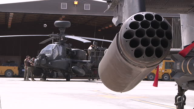 exterior shots apache helicopter on runway missile tips on side vehicle soldiers working on military hardware in the background apache helicopter on... - アパッチヘリコプター点の映像素材/bロール