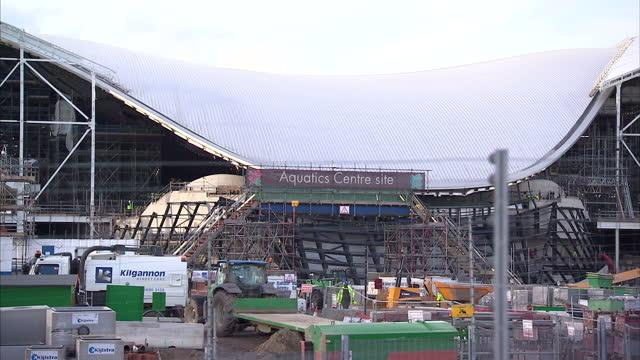 exterior shots aquatics centre construction site pan to olympic stadium olympic stadium aquatics centre construction at olympic park on february 22... - ロンドン オリンピックパーク点の映像素材/bロール