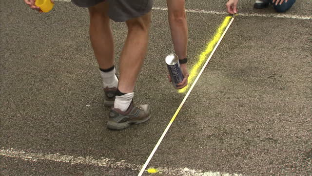 exterior shots archaeologists winding up tape measure & marking area of ground with spray paint. a council car park in leicester has become the... - tape measure video stock e b–roll