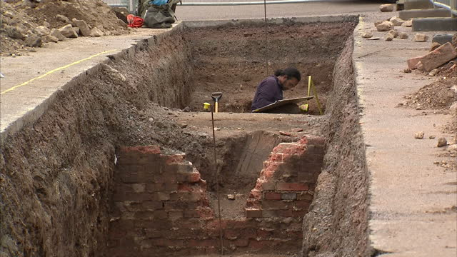 exterior shots archaeologists working on excavation site. exterior shots excavation dig site in car park. archaeologists searching under a car park... - archaeologist stock videos & royalty-free footage