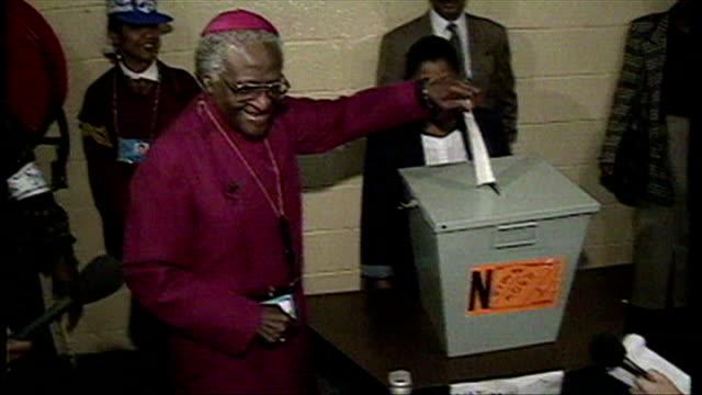 vídeos de stock, filmes e b-roll de exterior shots archbishop desmond tutu arrives in johannesburg to vote places vote into ballot box - desmond tutu