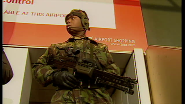 exterior shots armed police officer and armed soldiers in military combat uniform standing outside heathrow terminal building as part of increased... - military uniform stock videos & royalty-free footage