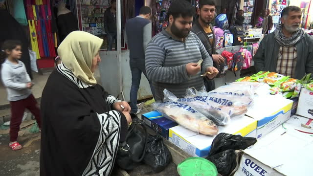 Exterior shots around a busy Mosul marketplace with people shopping for various produce including vegetables nuts and a man showing a kind of ration...