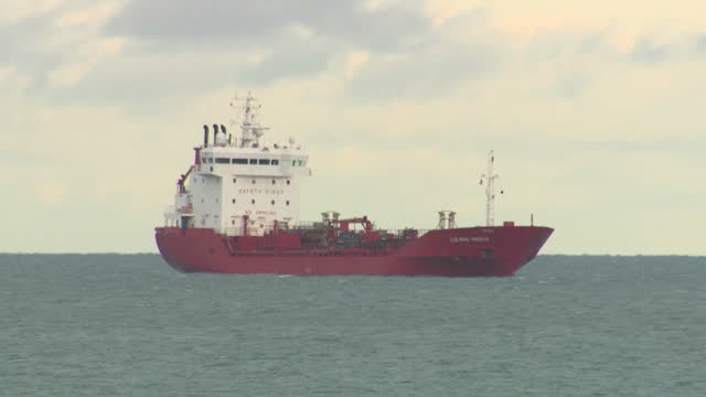 Exterior shots around Dun Laoghaire harbour area with large tanker ships moored at sea people strolling along harbour walls a fort and views over the...