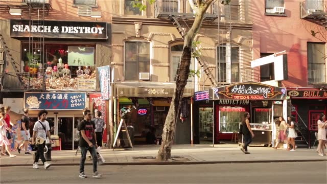 exterior shots around the east village district of manhattan new york, new york shot on june 24th, 2015. shots commuters and tourists walk along the... - tattoo stock videos & royalty-free footage