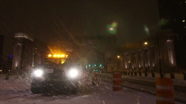 Exterior shots at night of cars driving around during a blizzard in New York City on Wide shots of snow plows plowing snow in Manhattan Wide shot of...