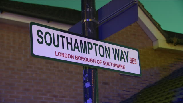 stockvideo's en b-roll-footage met exterior shots at night of the road sign 'southampton way' including shots of police officers stood on guard near cordon tape at the crime scene... - peckham