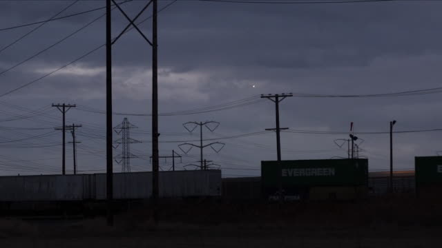 Exterior shots at night time of a freight train passing through rural Utah at night time with snowy mountain range in the background on 20 January...