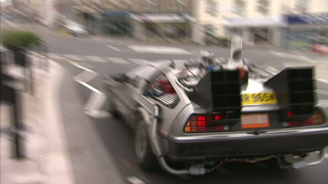 exterior shots back to the future replica delorean dmc 12 driving along road and through busy town centre. on october 21, 2015 in bristol, england. - macchina del tempo video stock e b–roll