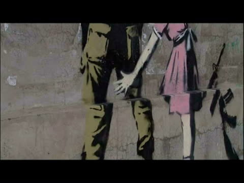 exterior shots banksy graffiti paintings murals on west bank walls general shots men at work putting up banksy art on wall - west bank stock videos & royalty-free footage