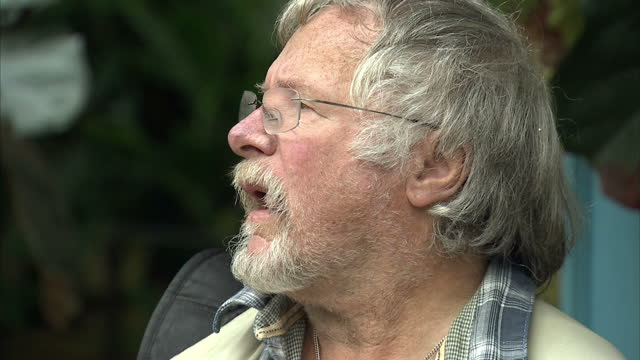 vídeos y material grabado en eventos de stock de exterior shots bill oddie stands holding laptop with his twitter account open listening to birds during a visit to london zoo. did you wake up to the... - bill oddie