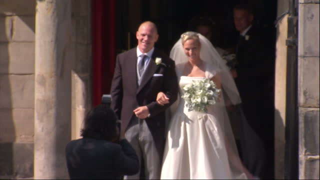 Exterior shots Bride Groom Mike Tindall Zara Phillips stand on Canongate Kirk church step pose for photographer kiss then walk out followed by...